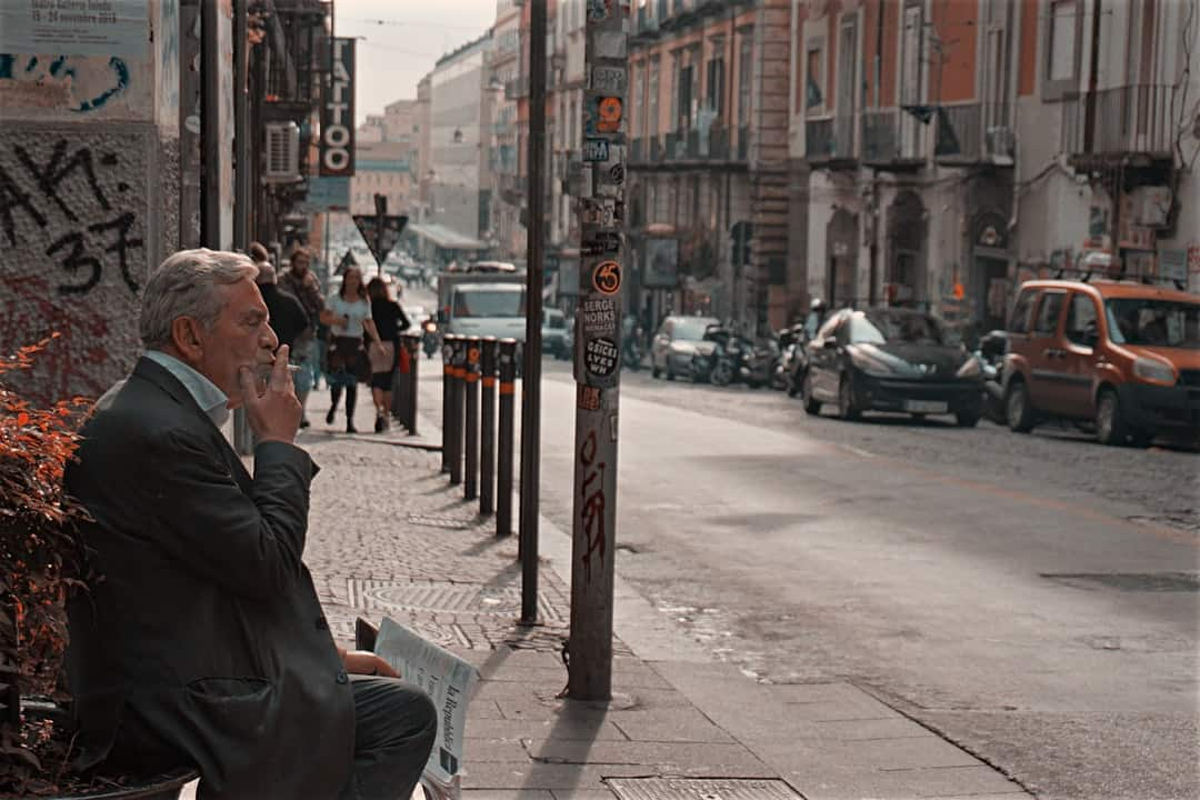 A person walking down a city street talking on a cell phone